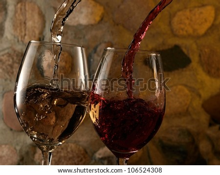 White and red wine flow in two glasses