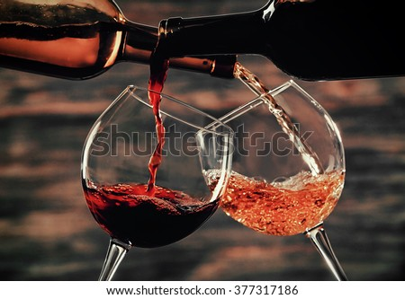 White and red wine pouring in glasses on wooden background