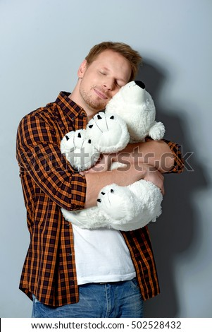 white and soft teddy bear in arms of a man #502528432