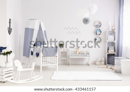White and spacious baby room with decorations in marine style