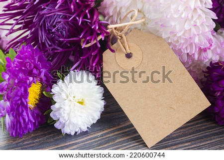 white and violet aster flowers with paper tag  close up  on wooden table