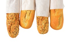 white and whole grain baguettes in paper bags