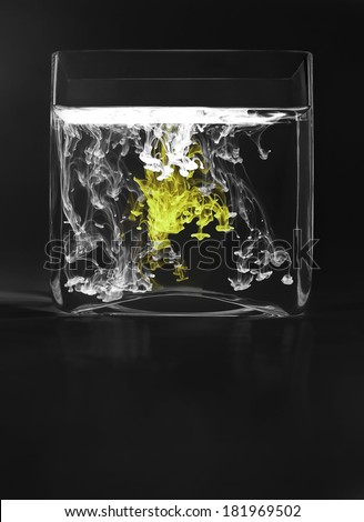 White and yellow ink drops in glass vase with water