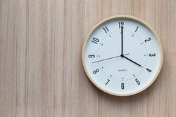 white and yellow plastic clock on light wooden wall. show time in late afternoon or evening time.