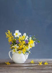 white and yellow spring flowers in teapot  on wooden table on blue background