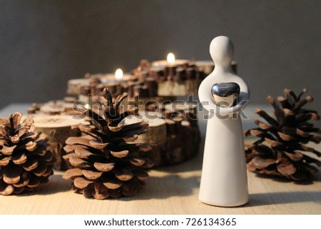 White angel figure with heart on background wooden candlestick. Gray background.