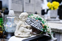 White angel figurine and grave candles on tombstone. Memory and sadness. All Saints Day.