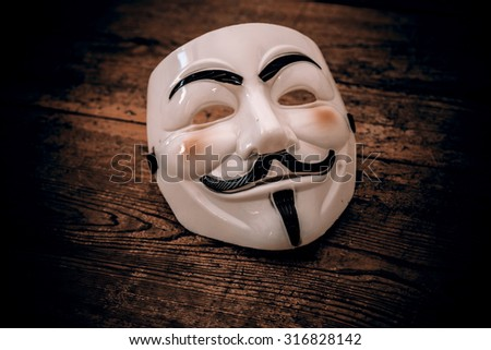 white anonymous mask on wood