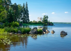White antique pavilion building temple of Neptune in Mon Repos landscape by the lake, Vyborg
