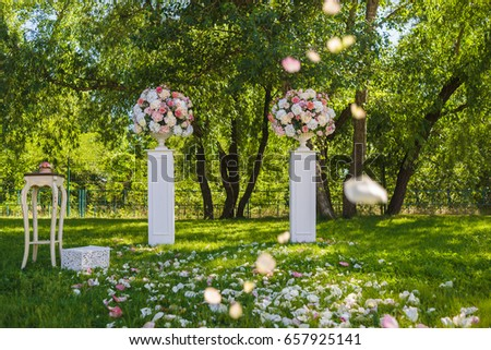 White antique vases with tenderness flowers and vintage table stand on the lawn grass in the garden. Wedding ceremony #657925141