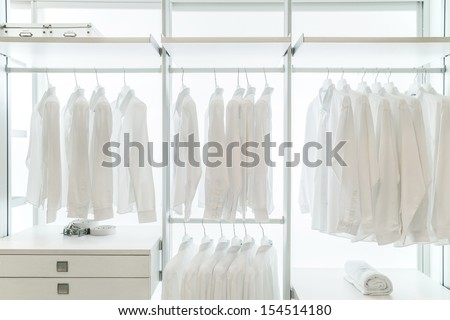 White apparels in built in white wardrobe with racks, drawers, and coat hangers