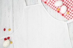 White apron template on wooden background with Easter eggs, copy space. Kitchen, cooking clothing mockup.