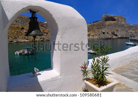 White arch with bell with view of Saint Paul's bay near Lindos, Rhodes, Greece