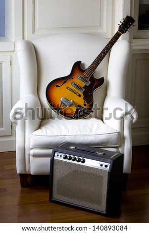 White armchair with an electric guitar and his amplifier. Electric Guitar and Amplifier .