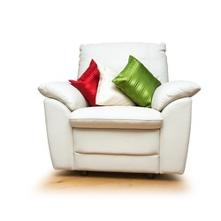 White armchair with colorful pillows isolated on white background. Object with clipping path