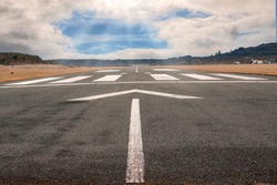 White arrow on a small asphalt air plane runway. Cloudy sky with small blue opening in the middle. Sun rays and flare. Small airport on the right. Aviation industry theme. Selective focus