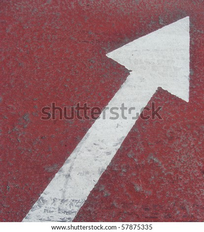 white arrow on red on a pavement sidewalk