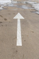 White arrow on the asphalt. Snow, puddles with water. Pointer concept.