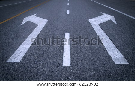 White arrow signs on asphalt