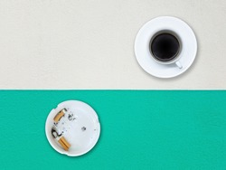 White ashtray. There are 3 cigarettes that have been extinguished inside and Black coffee in a white cup. Placed on a cement floor painted white and blue.