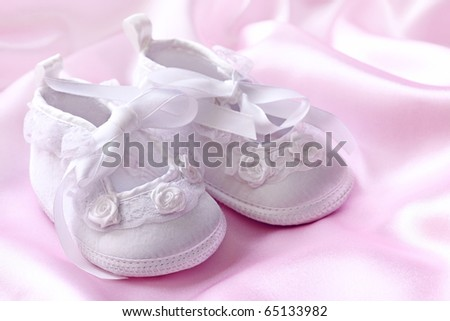 White baby booties with pearls on pink