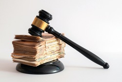 white background on a judge's hammer supported by a large number of banknotes positioned on top of each other