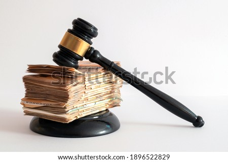 white background on a judge's hammer supported by a large number of banknotes positioned on top of each other ストックフォト ©