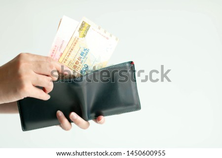 White background photo of hands holding a short wallet and another hand bring Hong Kong money (currency of Dollar Hong Kong or HKD) from the wallet to pay for something.