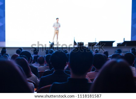 White Background Wall Screen for Presentation. Presenter Presenting on Stage at Conference Auditorium Hall Exhibition. Lecture Speaker. Blurred De-focused Unidentifiable Presenter and Audience.