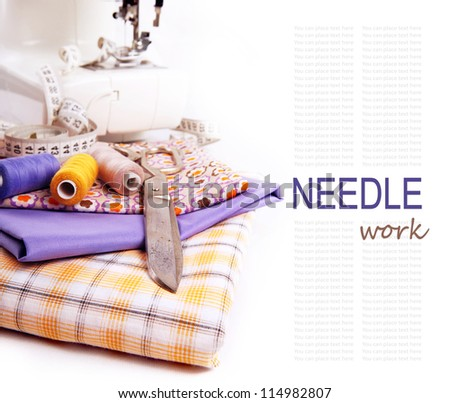 White background with colored fabric, thread and other sewing tools