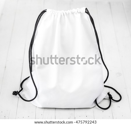 white backpack with black string on planked surface Foto stock ©