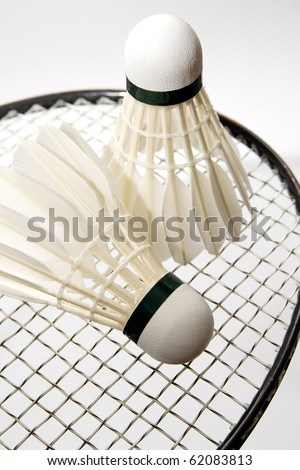 White badminton shuttlecocks on the racket