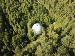 White ball in the forest top view. Green forest and road. Photo from the quadrocopter from the air.