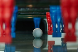 White ball on fussball table between players