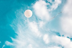 White balloon in blue sky background. Concept for freedom, following dreams or making a wish.
