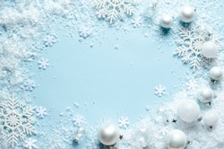 White balls and snowflakes on pastel blue background. Flat lay, top view. Christmas composition.