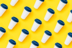 White bamboo coffee to go cup with a blue color silicone lid on a yellow background. Diagonal isometric view. Flat lay. New Year eco friendly and zero waste classic concept. Seamless pattern