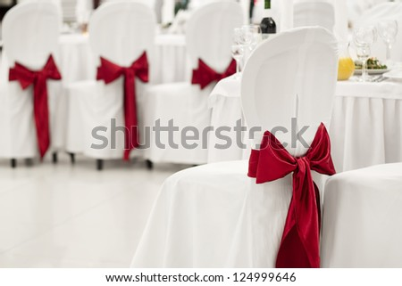White banquet chair with a red bow in the banquet hall