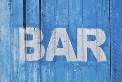 White bar sign painted on a dilapidated blue wooden wall