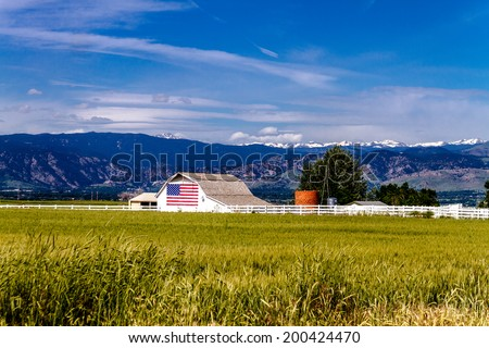 White barn with American flag painted on the side in front of growing wheat field near Rocky Mountains