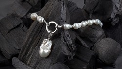 White baroque pearl necklace with pendant on black coal background. Close-up shot