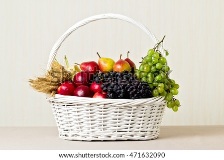 White basket with grapes, apples and pears.