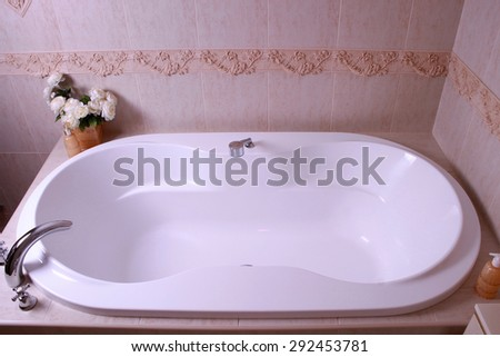 white bath tub with faucet and beige tiles in bathroom