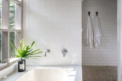 White bathroom interior, built bathtub, vase on top near wooden window frame with green plants on background, two dry, clean and fresh towel on wall hanger
