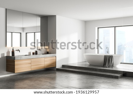 White bathroom interior with concrete floor, white bathtub and two sinks, side view. Minimalist bathroom with modern furniture and city view, 3D rendering no people