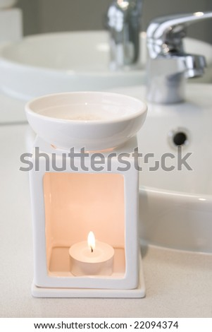 White bathroom oil burner next to basin - stock photo