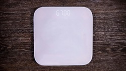 white bathroom scales on wood background