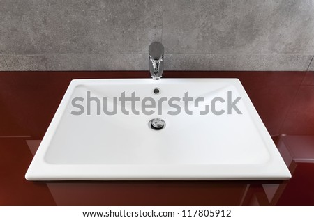 White bathroom sink on a red translucent board