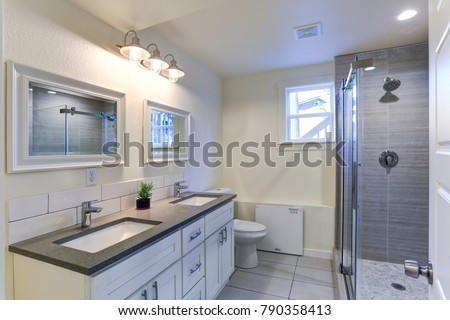 White bathroom vanity with granite top, double bath sinks, double wall mirrors and shower with glass door.