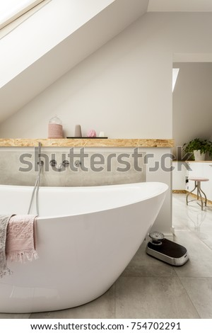 White bathtub next to a shelf with candles in monochromatic bathroom in the attic #754702291